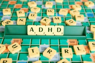 Scrabble bord met letters op plankje wordt ADHD gespeld