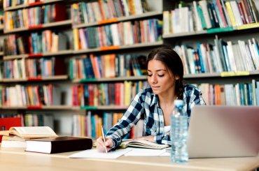 Student is aan het schrijven in de bieb