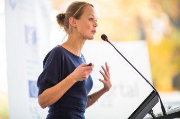 Vrouw spreekt in microfoon mensen toe