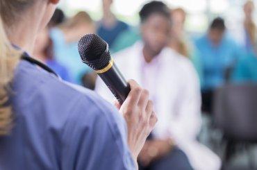 Student spreekt publiek aan door microfoon