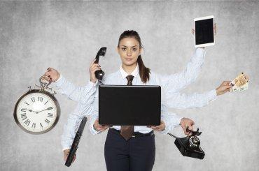 Junior medewerker achter laptop met heel veel armen en attributen