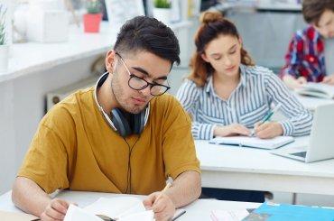 Drie studenten aan het werk in een klaslokaal achter bureau