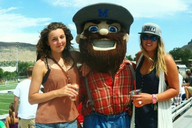 The Colorado School of Mines mascotte posing with two students.