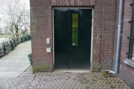 The door of the alternative entrance at the Bijlhouwerstraat 6-8. A green door that looks heavy.