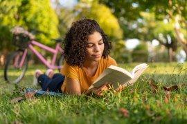 Student leest boek in gras