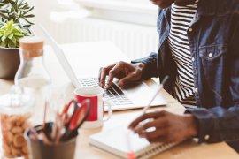 Student achter laptop met notebook erbij