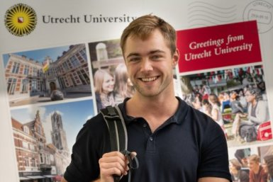A boy with a blue shirt in front of a large postcard saying 'Greetings from Utrecht University""