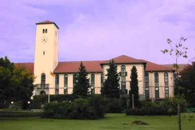 One of the buildings of Rhodes University, amids trees and pasture.