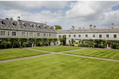 Buildings surrounding a field of grass in typical English college style at the University College Cork.