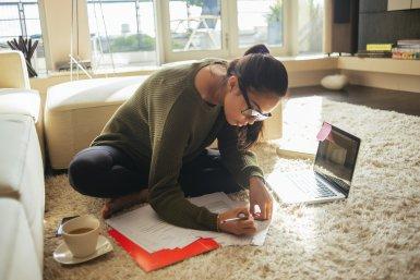 Student op een laptop op de grond