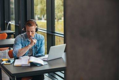 Jongen aan het studeren op zijn laptop in een moderne bibliotheek_nadenkend