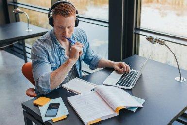 Jongen studeert in de bibliotheek met koptelefoon