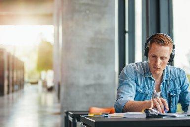 Jongen aan het studeren op zijn laptop in een moderne bibliotheek_zonlicht