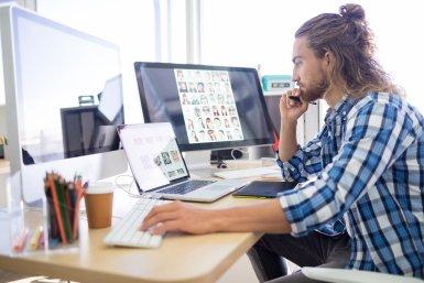 Jongeman werkt achter een computer met een grafisch ontwerp