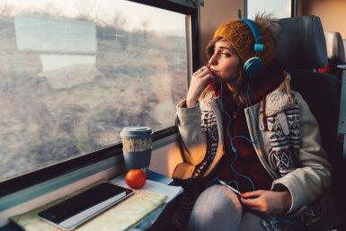Jonge vrouw in trein kijkt uit het raam