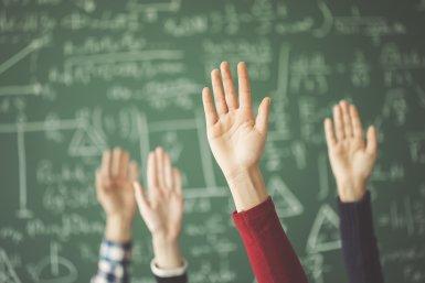 Handen omhoog voor schoolbord met formules